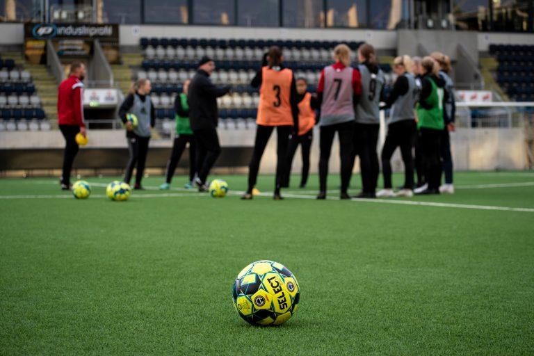 En fotboll i förgrunden, elever på fotbollsplan i bakgrunden