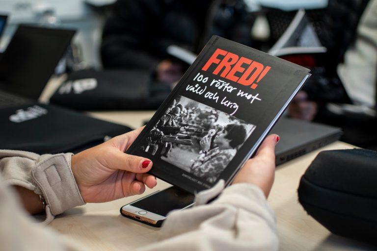 Elev håller i bok med rubrik FRED!
