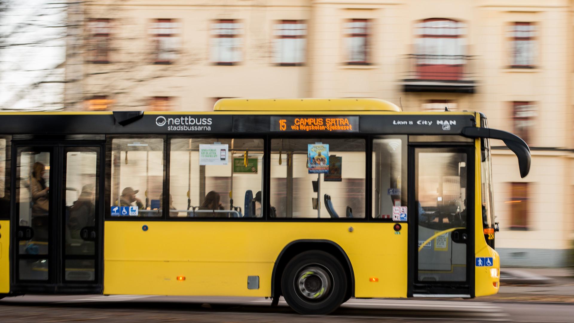Stadsbuss åker förbi ett hus i bakgrunden
