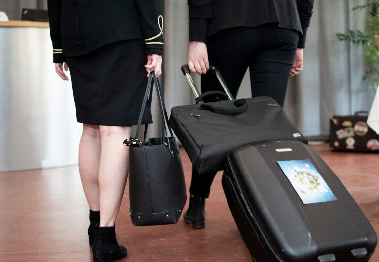 Två personer i uniform drar kabinväskor.
