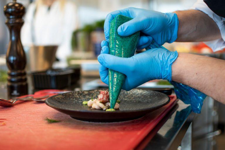 Elev från Restaurang- och livsmedelsprogrammet gör en snygg uppläggning på tallrik.