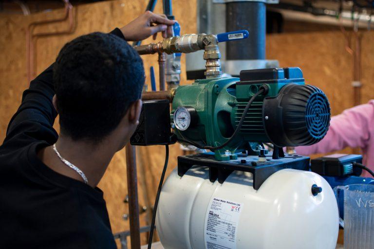 Elever på VVS- och fastighetsprogrammet kontrollerar en pump.