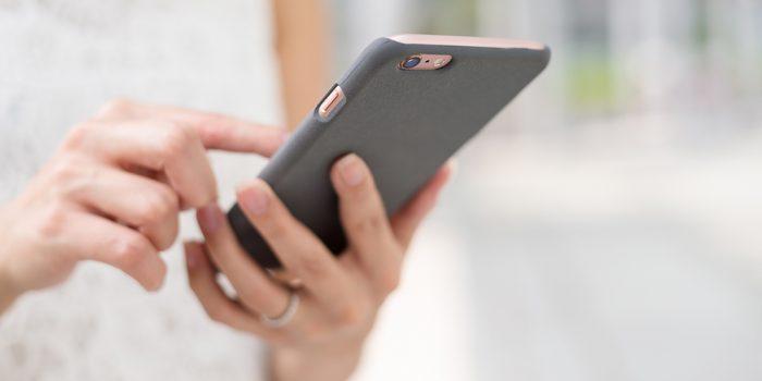 Kvinna skickar ett meddelande på mobiltelefon.