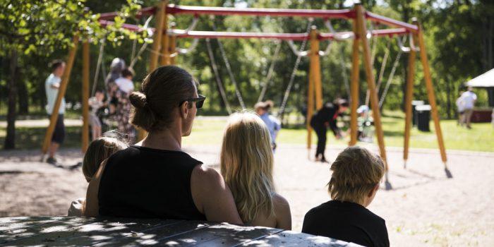 Pappa och barn som sitter på bänk vid lekplats.
