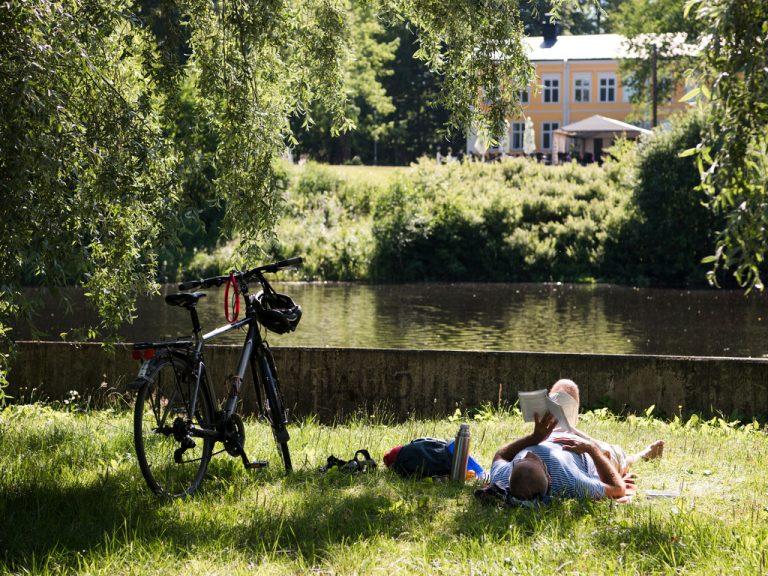 Man som ligger och läser i gräset i  Boulognern.