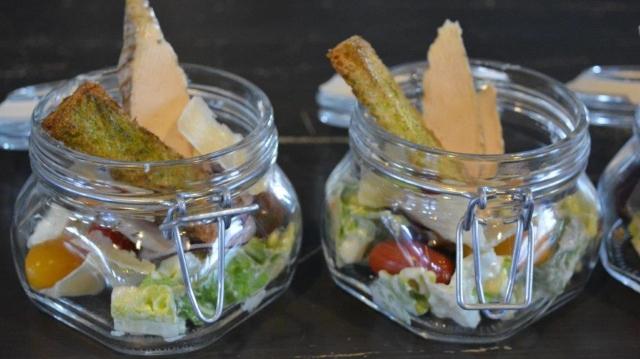 Sallad serverad i glasburk med brödkrutong och ost.