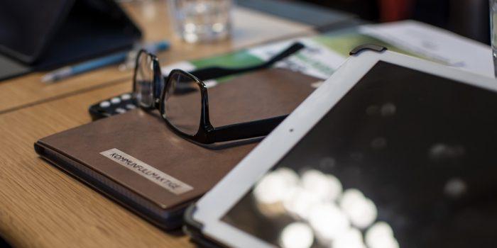 Möte kommunfullmäktige, glasögon och anteckningar på ett bord.