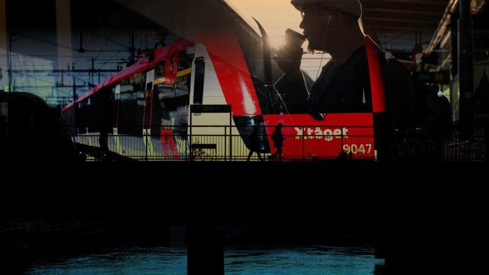 Tåg och pendlare vid station.