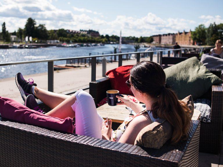 Kvinna som fikar på uteservering vid Gävle strand.