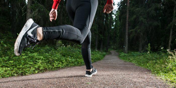 Närbild på ben som springer i ett motionsspår.