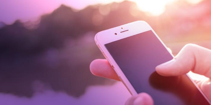 Närbild på hand som håller i en mobiltelefon.