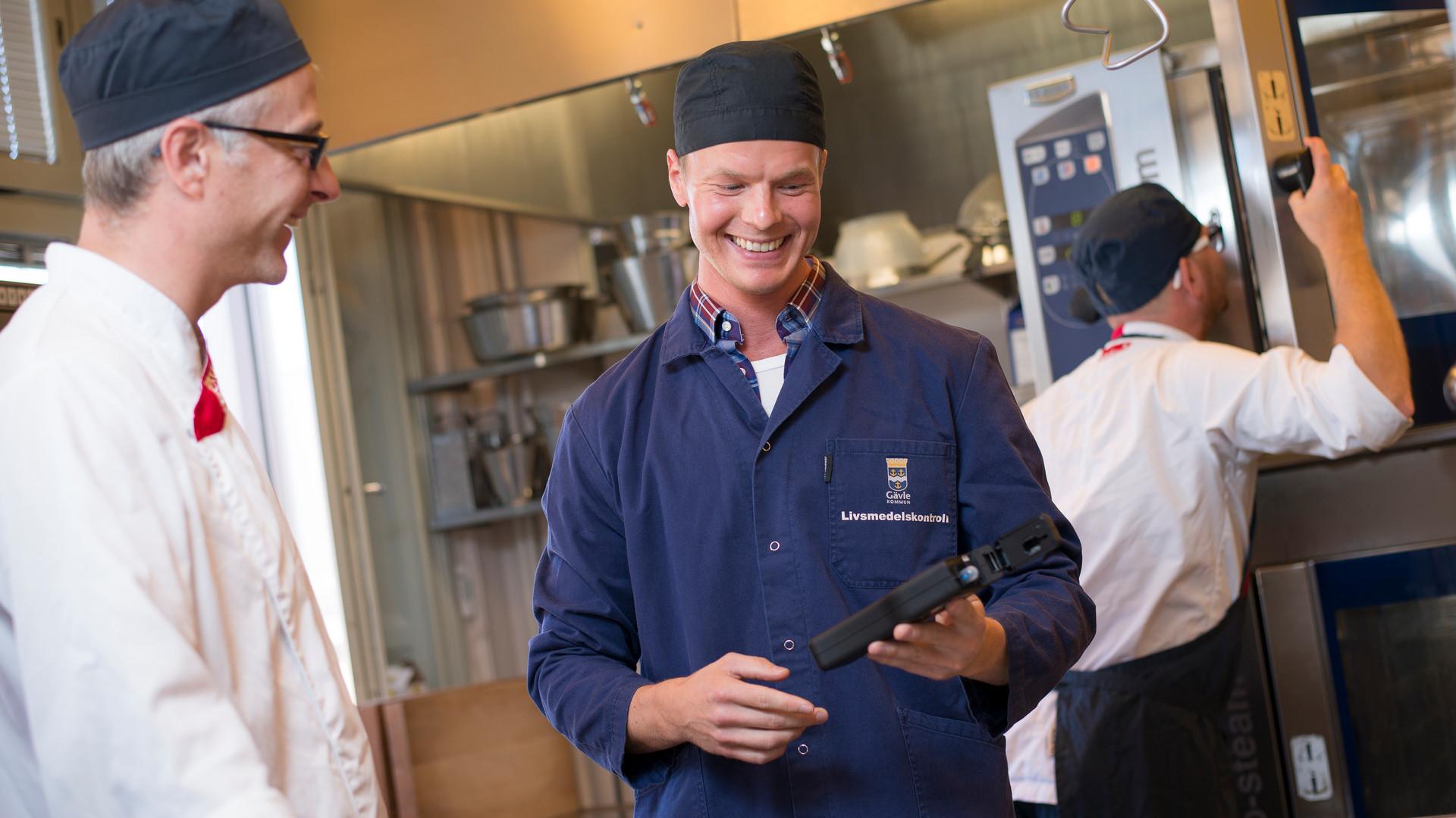 Glada män i restaurangkök.