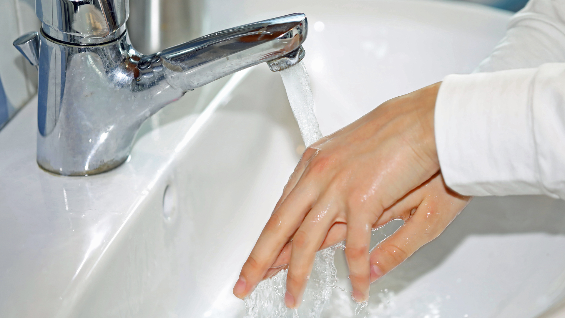 Händer som tvättar sig i vattenkran.