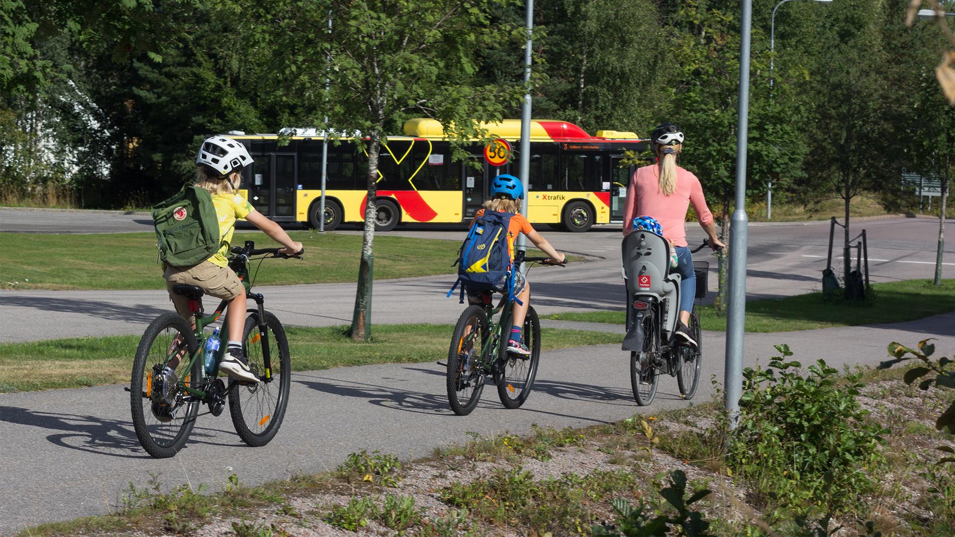 Tre barn och en vuxen kvinna cyklar på en cykelväg i sommarmiljö