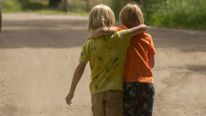 Två barn går längs en grusväg med armarna om varandras axlar.