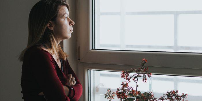 Orolig kvinna tittar ut genom ett fönster