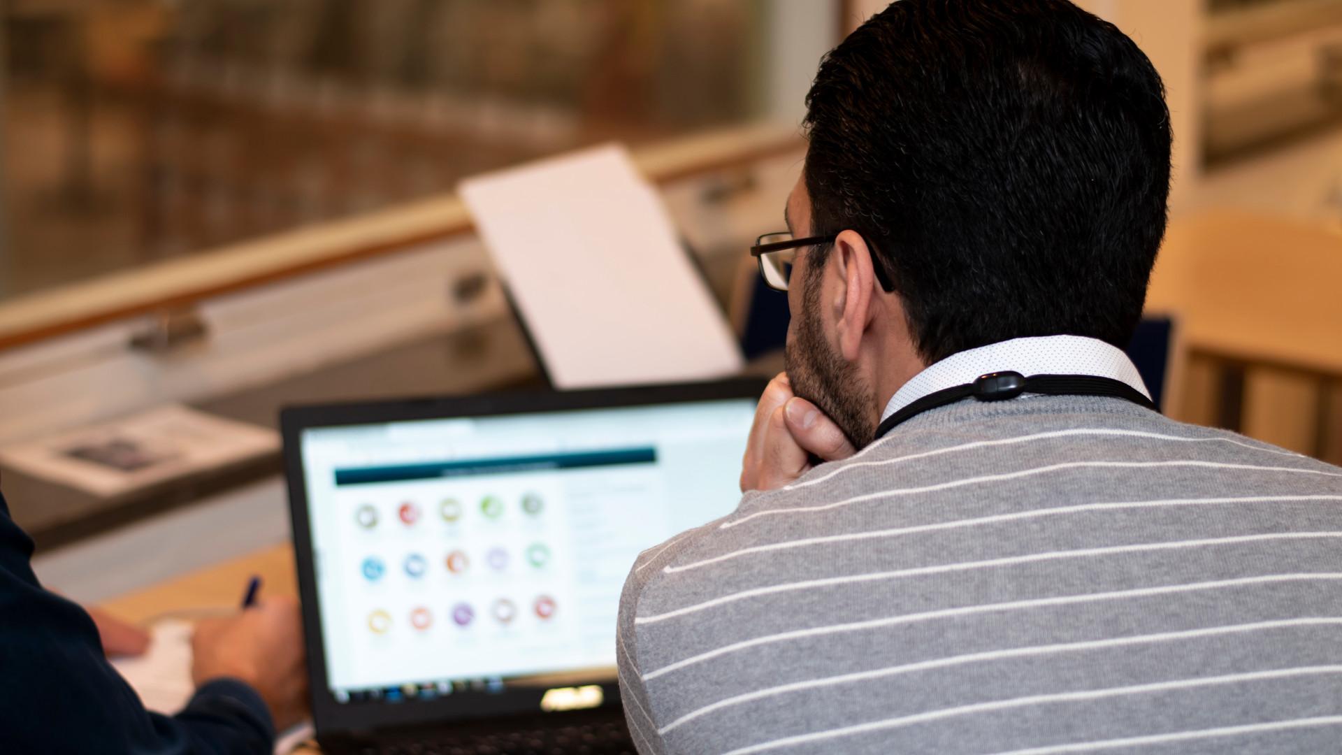 En person sitter framför en bärbar dator, med ryggen vänd mot oss..