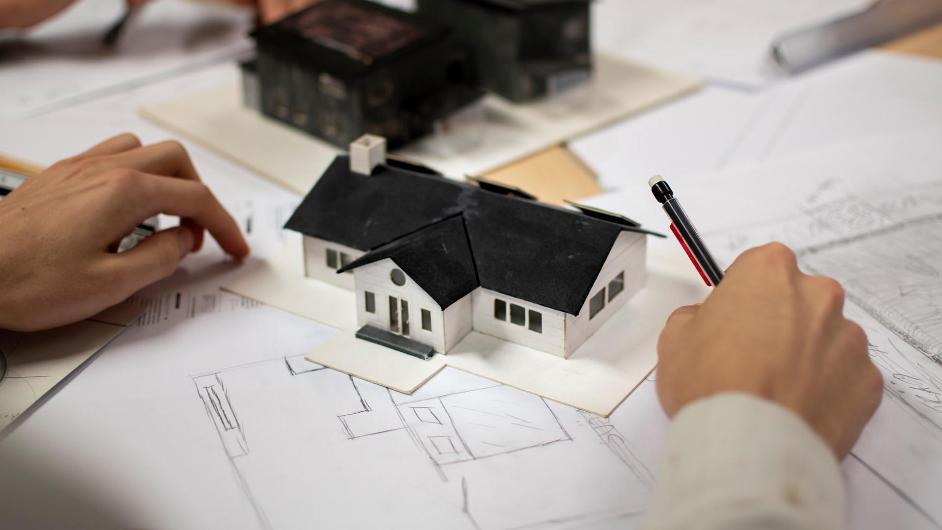 Närbild på arkitekturskisser och en husmodell i papp
