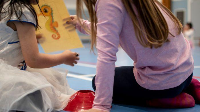 Barn som sitter på ett gymnastiksalsgolv och tittar på en teckning
