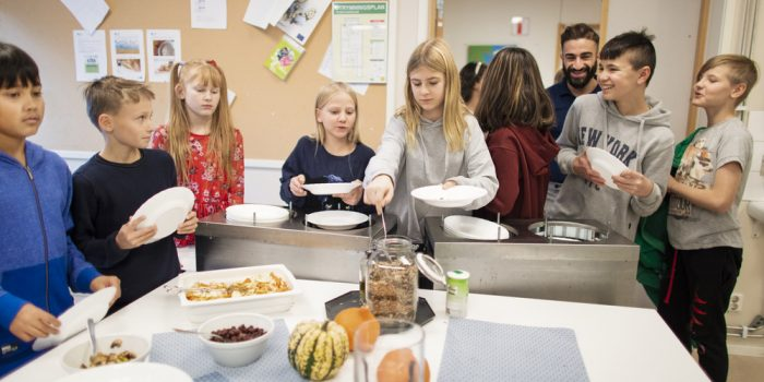 Skolbarn står i matsal