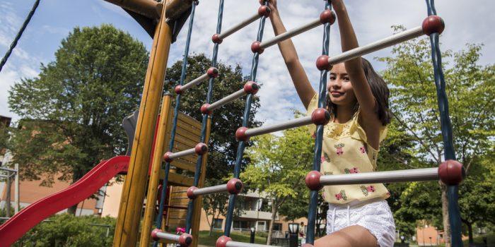 Flicka som klättrar på lekplats.