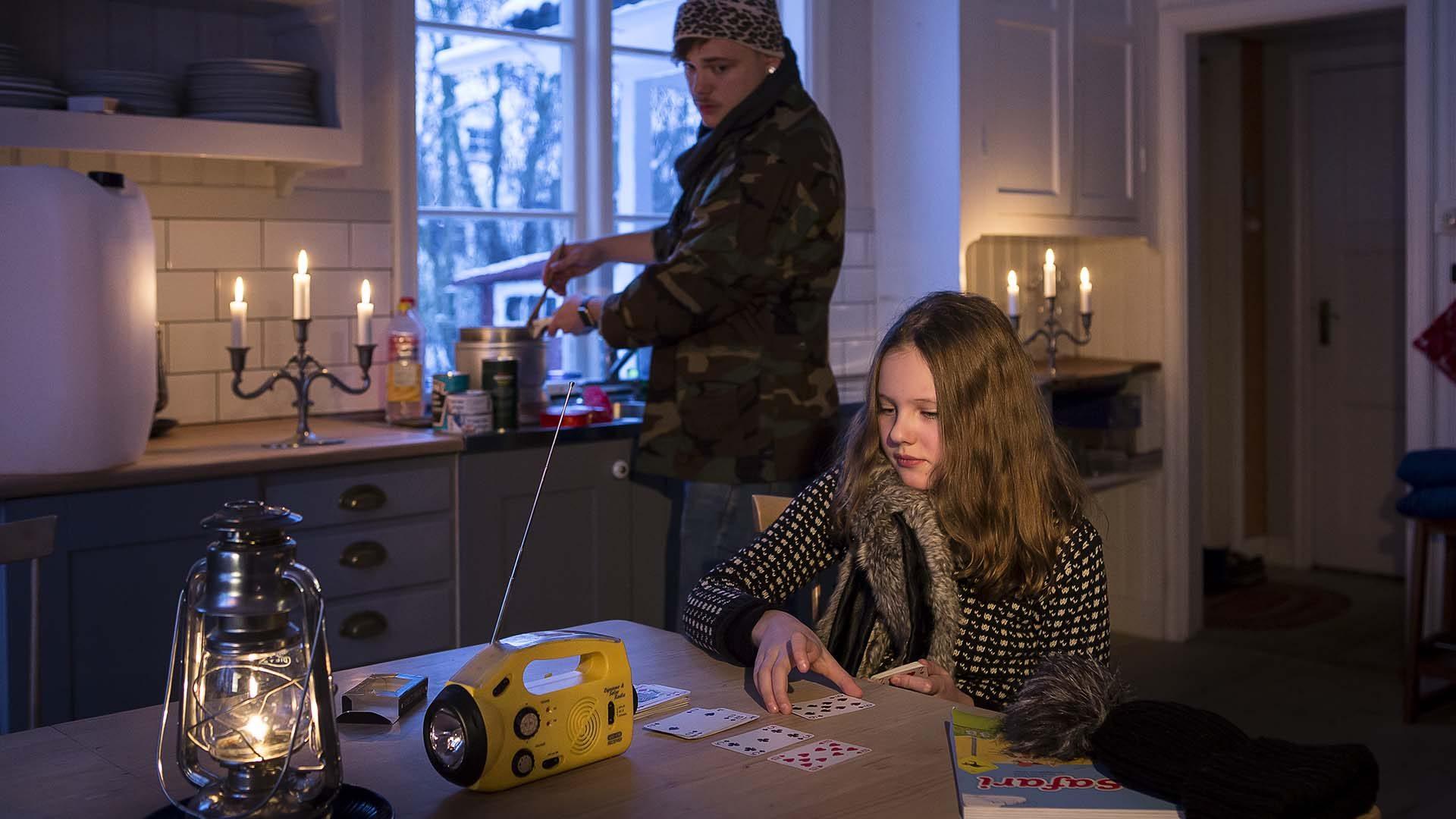 Två personer i ett kök med ficklampa och levande ljus