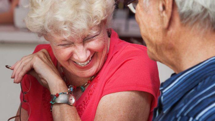 Äldre kvinna skrattar tillsammans med en äldre man.
