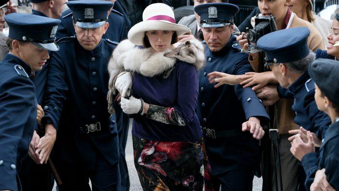 Kvinna i päls och hatt förs fram i handfängsel av en grupp poliser medan journalist tar kort med kamera av äldre modell.
